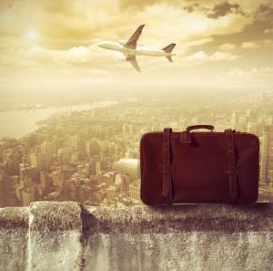 самолет и чемодан на фоне города
